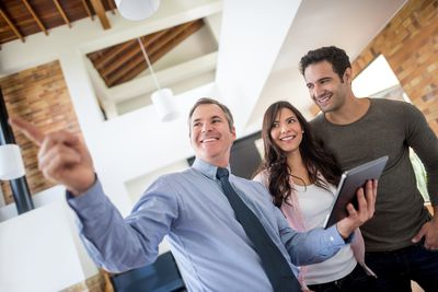 young couple looking at home with a real estate agent