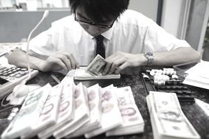 Chinese worker counting American currency