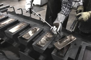 Workers forge gold bullion into bars with casting molds.