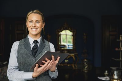 A concierge standing inside a hotel, holding a digital tablet, ready to help