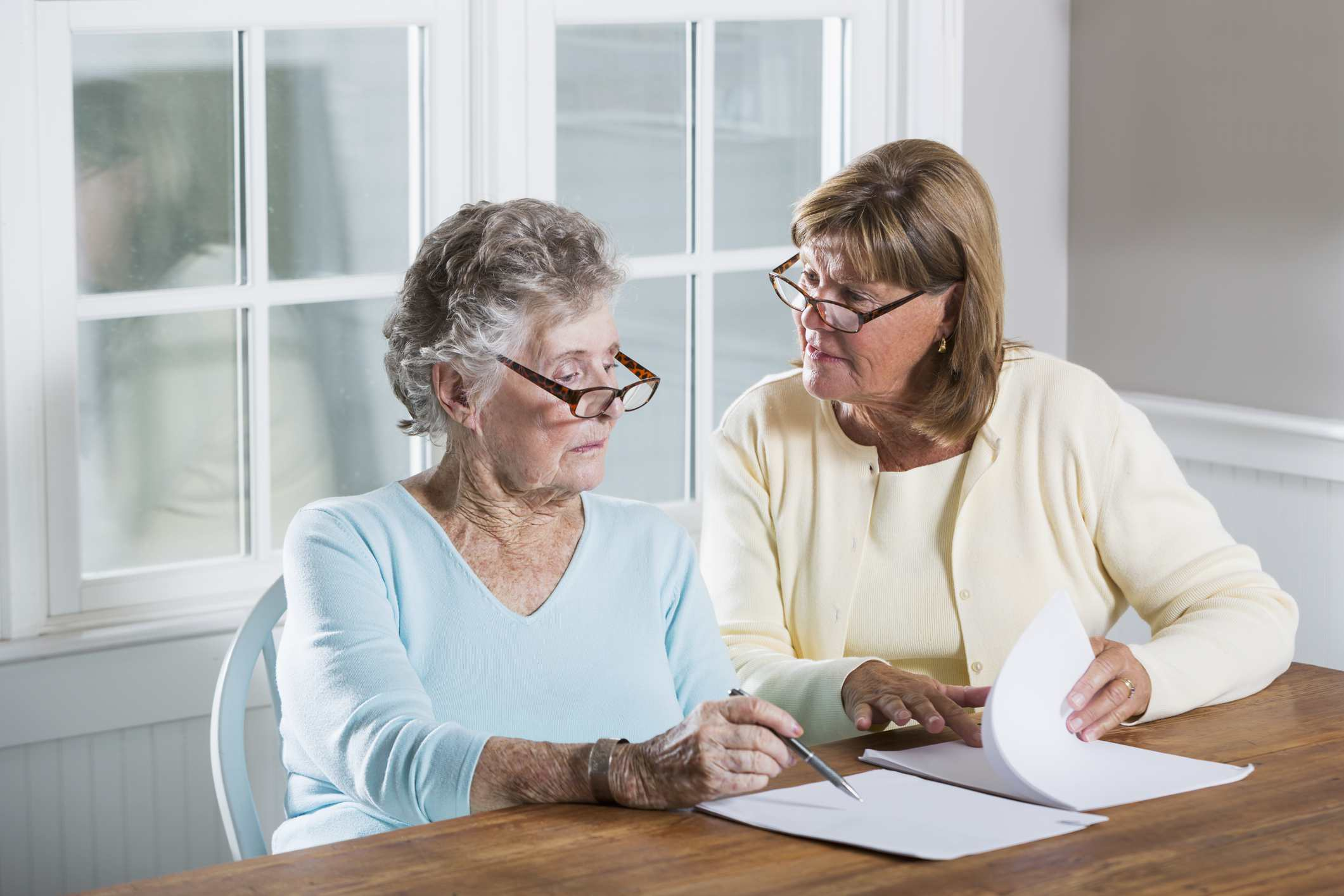 A woman helping her elderly mother with paperwork.