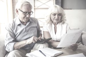 Older couple seated on a sofa with a calculator discussing their estate tax liability