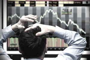 Man starting at stock market graph trying to make decisions