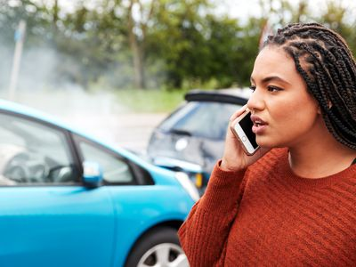 Female motorist calling insurance company next to a car accident in background