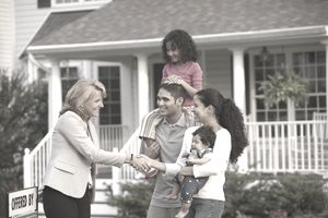 Family shaking hands with real estate agent in front of house - stock photo