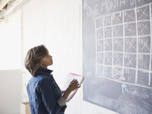 Woman with folders in her hands looking at a calendar written on a blackboard