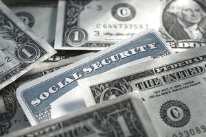 Closeup of a Social Security card surrounded by dollar bills, the result of collecting spousal benefits