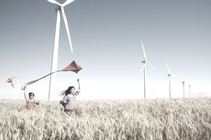 girls playing with kite in wheat field, wind turbines in background