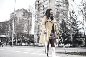 Woman with cast on foot walks using crutches