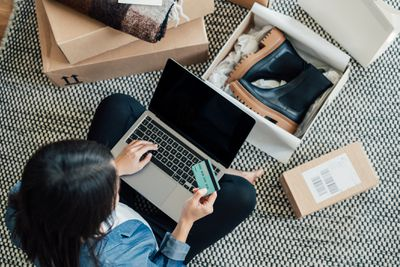 Person sits on rug with computer and credit card. Shoe boxes from an online shopping purchase are in front of them.