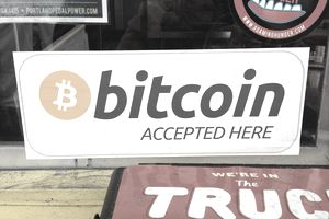 "Sign in a merchant's window reads, ""Bitcoin accepted here."""
