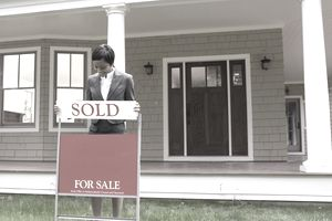 Realtor placing a sold sign in front of house