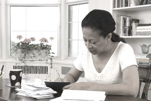 A woman writes a check in her home office