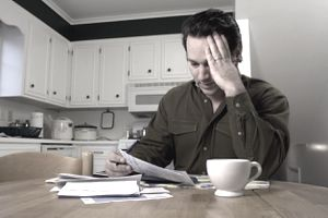 Stressed out man sitting at kitchen table looking at a stack of bills.