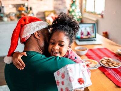 Child holding a gift hugging her father who's wearing a Santa hat