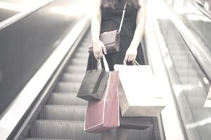 Woman descending on escalator with shopping bags that are adding to her debt