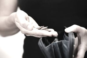 A woman holds a handful of coins over a change purse as if she is about to deposit them.