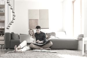 A couple sit on the floor of their living room using a laptop and binder to figure out how much they owe in direct taxes