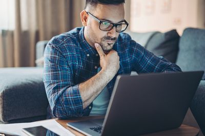 Man wearing glasses working on a laptop