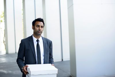 Young man in suit and tie walking out of a white building with a covered box after a layoff