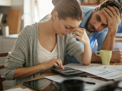 A man and a woman are paying bills. The woman is using a calculator. They both look stressed.