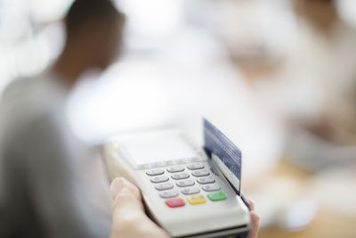Credit card being swiped through payment machine.