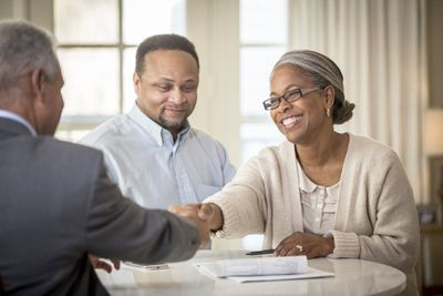 A smiling Black couple review paperwork with a mortgage broker.