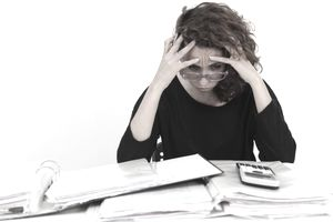 Distressed woman looking at piles of paperwork, a calculator, and a folder on her desk