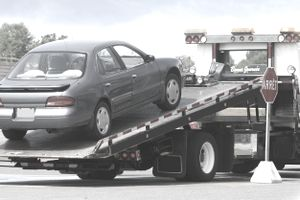 A repossessed car being loaded onto a flat-bed tow truck.