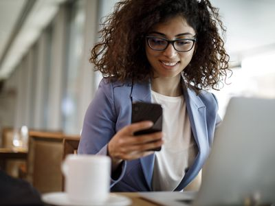 A young woman reviews financial information on her smartphone and laptop.