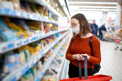 Young woman shopping in a grocery store and wearing protective medical mask