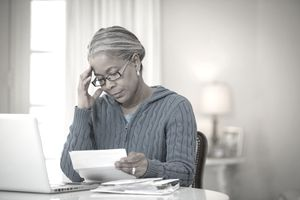 A woman looking concerned as she reviews documents about her 401(k) plan.