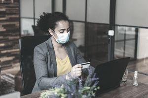 A woman in business clothing wearing a surgical mask for COVID-19 uses a new credit card with her laptop