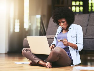 Black woman sits on hardwood floor in front of a couch with a laptop and a credit card in her hand.