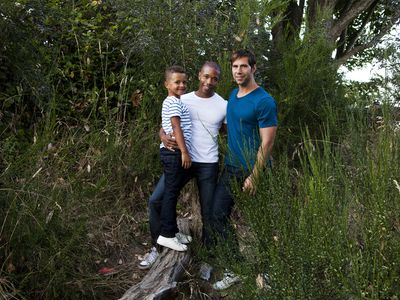 Portrait of homosexual, multiracial couple in a field with their son