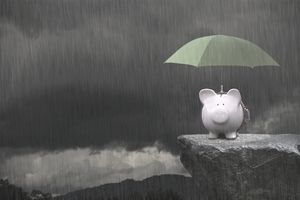 Piggy bank standing on a edge of a cliff in rain and covered by green umbrella