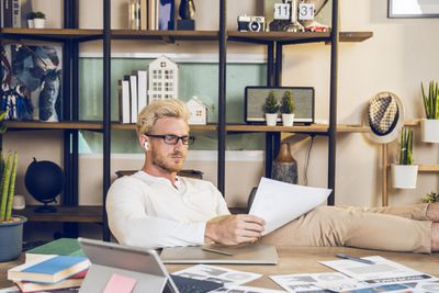 Young blond, bearded man reviewing papers at a desk with his feet up