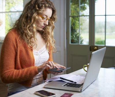 Woman with a calculator and computer creating a budget for irregular expenses