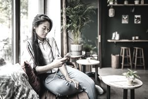 A cafe customer sitting by the window in her favorite cafe, using her smartphone and relaxing.