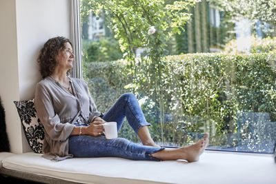 Middle-aged woman with curly hair sitting on window-seat cushion with tea mug looking out a window.