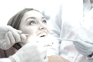 Woman Having Teeth Checked While Smiling at Orthodontist