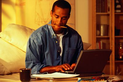 Man at Home Laptop Reading Papers and Typing With Pencil in His Mouth