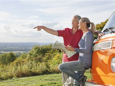 Retired couple looking at a map beside a camper van