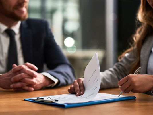 Man sitting at a desk while a woman goes over a contract on a clipboard.