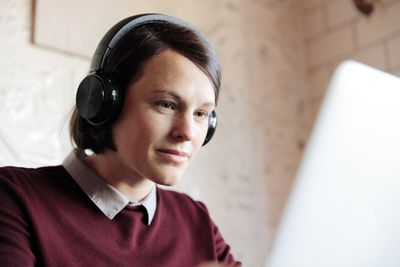 Young woman wearing headphones working on a laptop