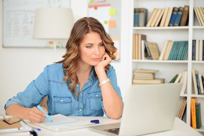 Woman seated in front of computer in her home office, writing notes