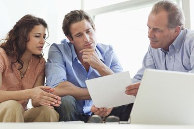 Couple going over paperwork with a financial advisor.