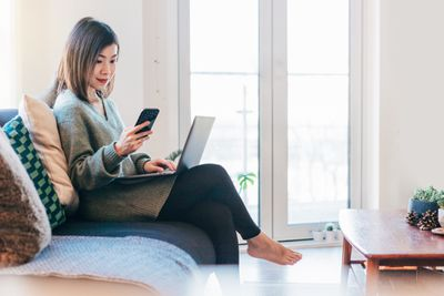 A woman sits on a couch with a laptop and a smartphone.