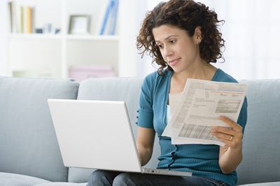 A woman holding papers looks at her computer