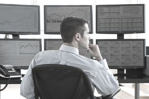 Stock trader analyzing markets on multiple screens